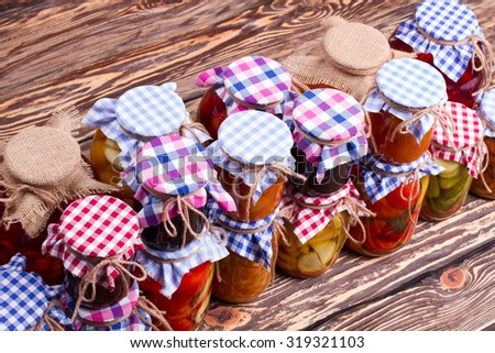 Beautiful canned in bright design on a wooden shelf. Canning food in glass jar. - stock photo
