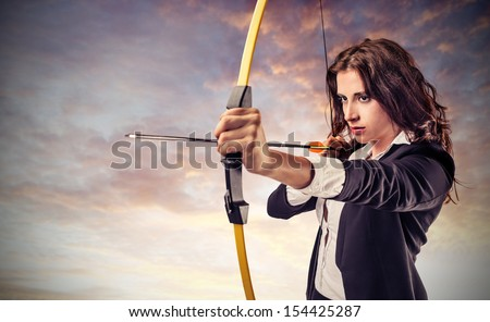 beautiful career woman pulls arrow with a bow - stock photo