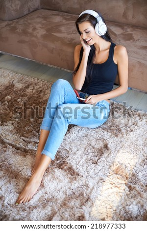Beautiful carefree woman listening to music relaxing barefoot on the carpet in the living room laughing with delight as she listens to the tunes  high angle view - stock photo