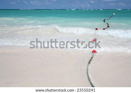 Beautiful Caribbean tropical beach with white sand and bouys floating in green ocean, suitable background for a variety of designs. FOCUS on waves rolling onto beach - stock photo