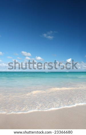 Beautiful Caribbean tropical beach with white sand and green ocean, suitable background for a variety of designs. FOCUS on edge of waves rolling onto the beach - stock photo