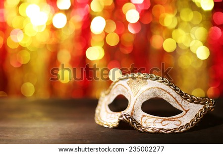 Beautiful carnival mask on table on bright background - stock photo