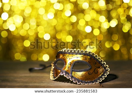 Beautiful carnival mask on table on golden background - stock photo