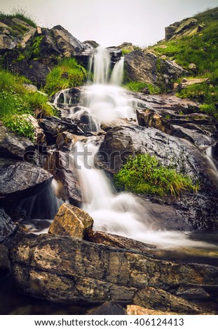 Beautiful cascading waterfall over natural rocks - stock photo