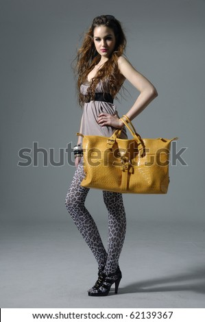 Beautiful casual model with a big posing on gray - stock photo