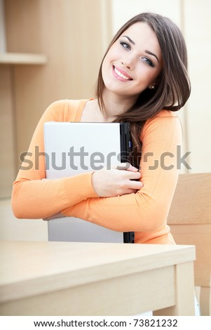 Beautiful casual woman hugging her laptop at home - stock photo