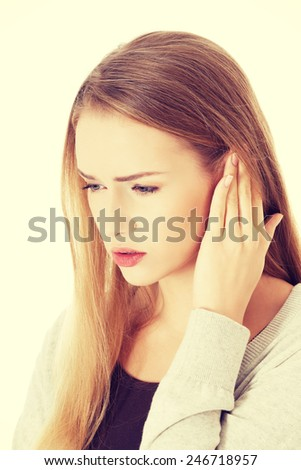 Beautiful casual woman is touching her ear. Health concept.  - stock photo