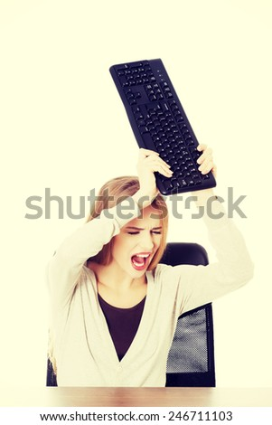 Beautiful casual woman trying to destroy keyboard.  - stock photo