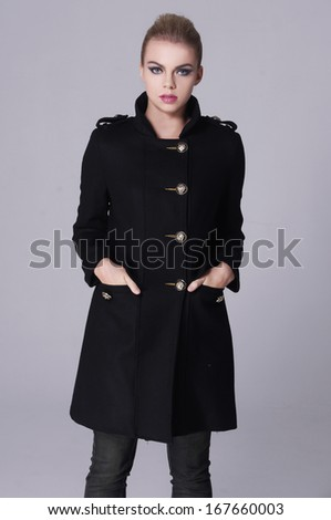Beautiful casual young woman in black coat  standing isolated against gray background - stock photo