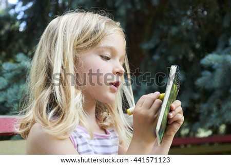 Beautiful Caucasian blond girl sitting on old park bench drawing picture - stock photo