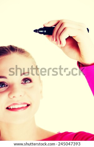 Beautiful caucasian blond woman writing on copy space. Focus on hand.  - stock photo
