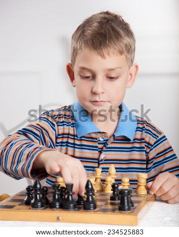 beautiful, caucasian boy playing chess  - stock photo