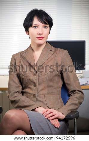 Beautiful caucasian brunette businesswoman in her office. - stock photo