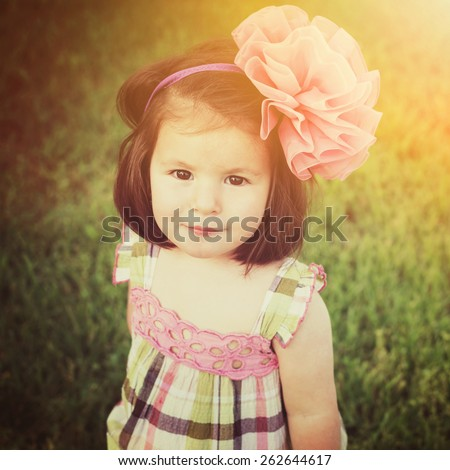 Beautiful Caucasian brunette toddler girl in nature in summer. Closeup portrait of cute little girl smiling looking at camera wearing pink and green dress and big pink bow headband. Square, retouched. - stock photo