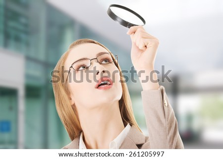 Beautiful caucasian business woman with magnifying glass - stock photo