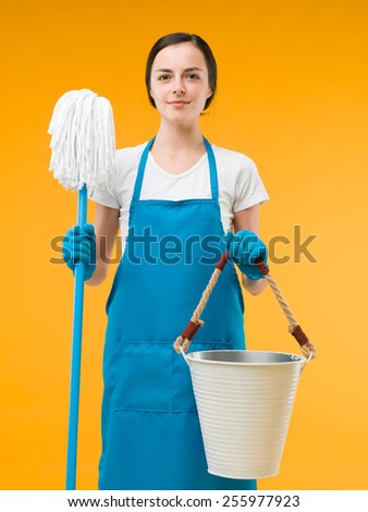 beautiful caucasian cleaning woman standing and holding mop and bucket against yellow background - stock photo