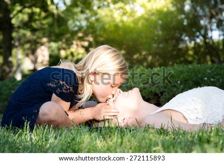 Beautiful Caucasian ethnicity daughter kissing her mother in the forehead at park - stock photo