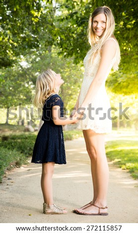 Beautiful Caucasian ethnicity mother and daughter bonding at park with mom looking into camera - stock photo
