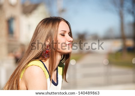Beautiful caucasian girl dreaming. Outdoor portrait. - stock photo