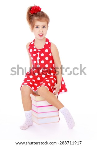 Beautiful Caucasian girl in a red dress with polka dots sitting on a stack of books-Isolated on white background - stock photo