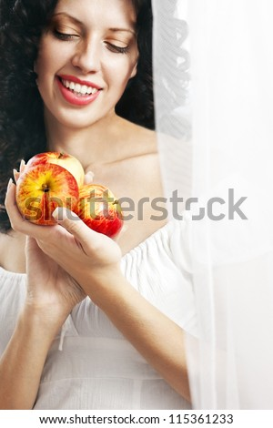 Beautiful Caucasian girl with three red apples in her hand smiling with perfect smile, half hidden by white veil. - stock photo
