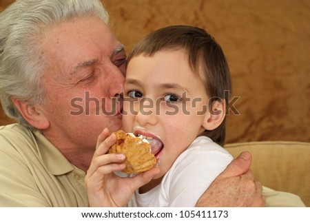 Beautiful caucasian grandfather with his grandson sitting on the couch on a brown background - stock photo