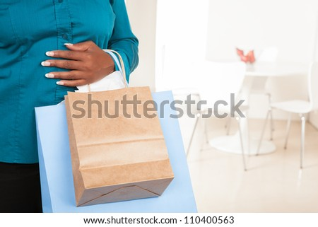 Beautiful Caucasian lady with long blond hair sitting on couch in living room wearing a blue shirt holding a white gift with a big silver bow - stock photo