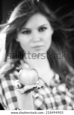 Beautiful caucasian long haired girl holding an apple, posing with dark background and contour light. Photo has grain texture visible on its maximum size. Artistic black and white photography  - stock photo