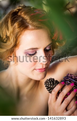 beautiful caucasian model with red curly hair looking down with a small smile holding an acorn and playing with her bracelets in the thick forest - stock photo