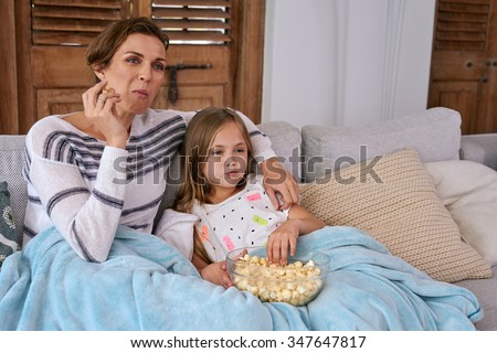 Beautiful Caucasian mother and child kid spending quality time sitting on sofa at their home eating popcorn and watching tv snuggling under blanket - stock photo