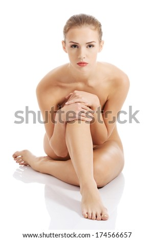 Beautiful caucasian naked woman sitting with fresh clean skin. Isolated on white. - stock photo