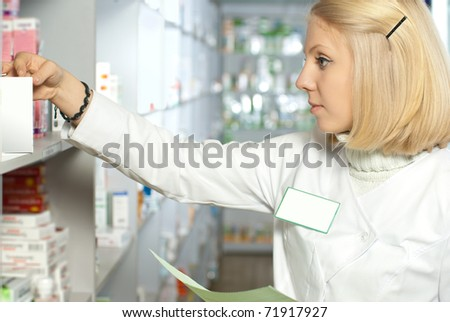 Beautiful caucasian pharmacist searching the right medicine - stock photo