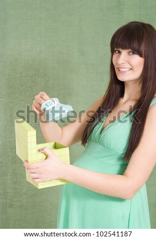 Beautiful Caucasian pregnant girl standing with bootees on white background - stock photo