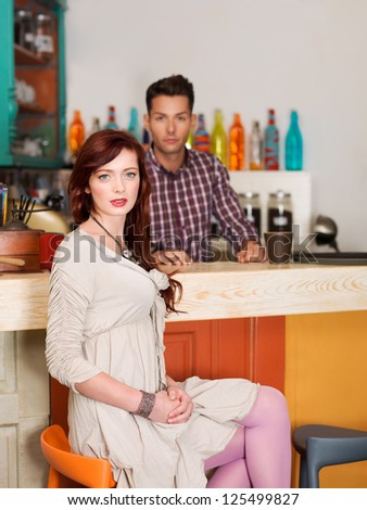 beautiful caucasian red haired girl sitting on a chair at the bar in colorful cafe with a barteneder behid the counter - stock photo