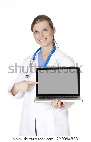 Beautiful Caucasian woman doctor holding a laptop computer and pointing at the screen isolated on a white background.  There is clipping path around the computer screen - stock photo