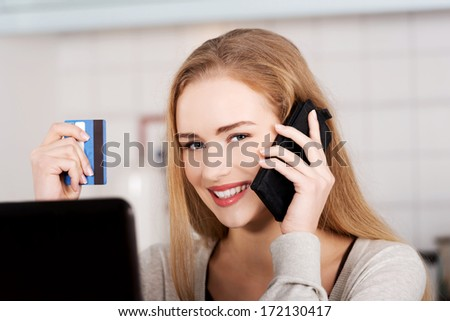Beautiful caucasian woman doing online shopping. She's holding credit card and phone. - stock photo