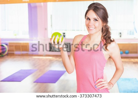 Beautiful caucasian woman fitness exercise, holding green apple. Eating, sport and healthy lifestyle concept - stock photo