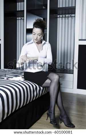 beautiful caucasian woman in a bedroom apply lotion on hands - stock photo