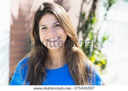 Beautiful caucasian woman in a blue shirt in the city - stock photo
