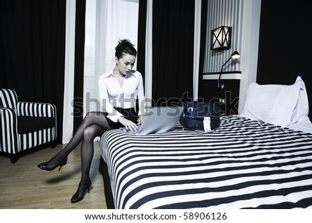 beautiful caucasian woman laptop computing in a hotel bedroom - stock photo