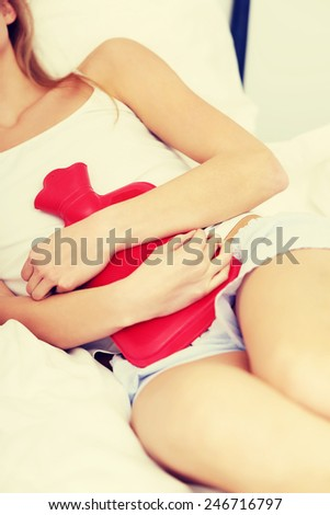 Beautiful caucasian woman lying in bed with hot water bag. - stock photo