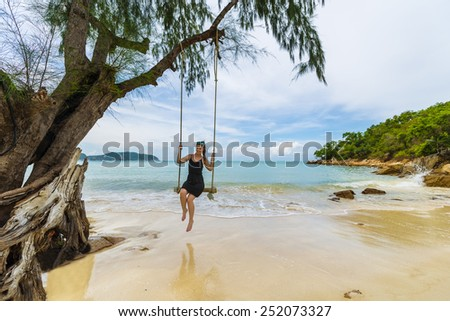 Beautiful caucasian woman on wooden swing tied to a tree with ropes, enjoying herself on a tropical beach in Thailand, Koh Phangan - stock photo
