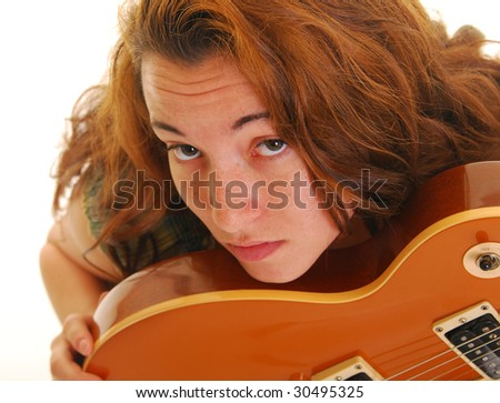 Beautiful caucasian woman resting her chin on side of a guitar. - stock photo