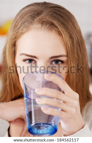 Beautiful caucasian woman sitting in the kitchen and drinking fresh water. - stock photo