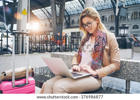 Beautiful Caucasian woman using net-book while sitting in train station interior. modern businesswoman using a laptop computer while waiting for the train. Flare light. - stock photo