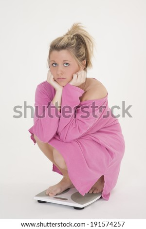 Beautiful Caucasian woman weighting herself and very upset about it - stock photo