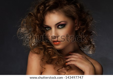 Beautiful caucasian woman with curls and evening makeup - stock photo