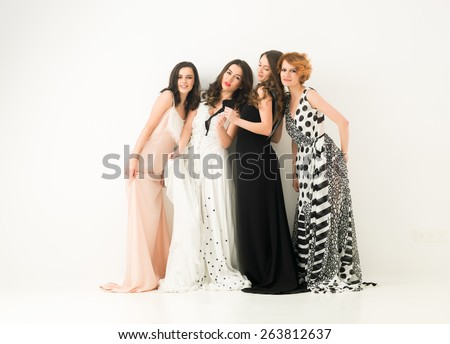 beautiful caucasian women in cocktail dresses posing together and having fun, against white background - stock photo