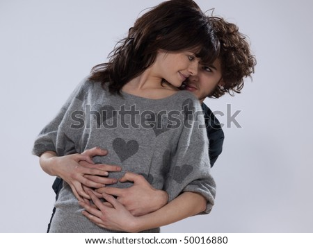 beautiful caucasian young couple wearing a sweater with hearts on it - stock photo