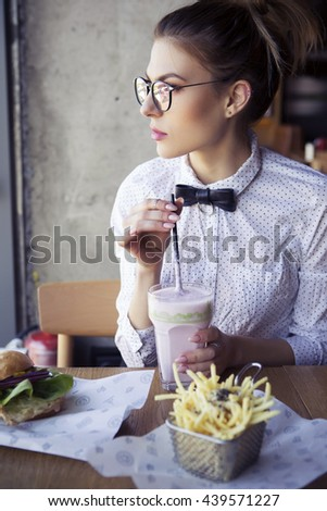 Beautiful caucasian young woman eating lunch fast food fried potato, burger and milkshake in cafe near sunny day. Wearing business style white shirt and glasses. Casual outfit, stylish interior - stock photo